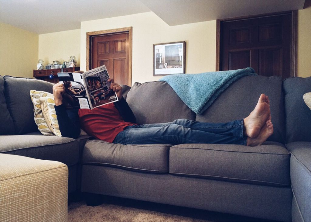 Man reading magazine on couch